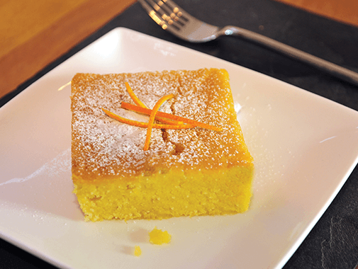 orange polenta cake served with orange zest strands on a dish