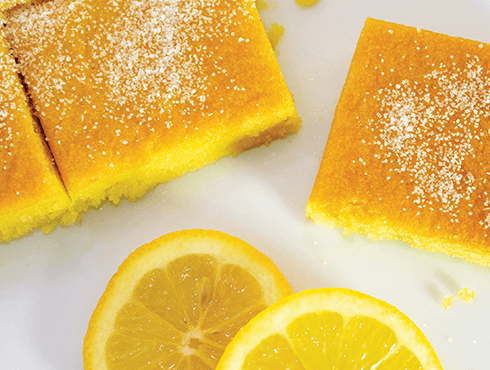 lemon drizzle cake served with slices of fresh lemon