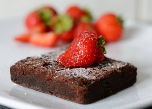 a moist chocolate brownie with a strawberry resting on top