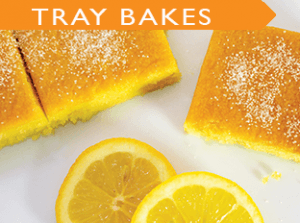 moist cakes laid out on a tray with fresh orange slices
